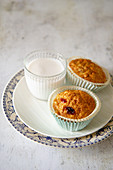 Muffins with raisins next to a glass of milk
