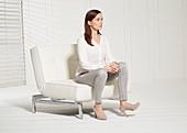 Sitzende Frau hebt Fußspitze an (Körpersprache Ablehnung)