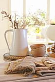Krug mit Zweigen und natürliche Deko auf dem Tisch