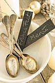 Alte Silberlöffel und Schildchen in weisser Schale auf Weihnachtstisch