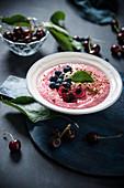 Vegane Smoothie Bowl mit Dinkel, Heidelbeeren, Kirschen, Mandeln und Roggenbrotkrümeln