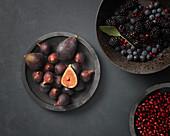 Frische Feigen, Beeren und Granatapfelkerne in Schalen