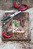 Cooked meat t-bone steak with red chili peppers, spices and fresh rosemary
