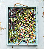 Okra, spicy peppers and small black corns on blue wooden tray