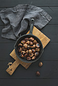 Roasted chestnuts in iron skillet pan