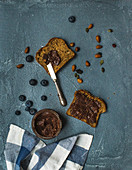 Whole grain bread toasts with organic vegan chocolate peanut butter, blueberry and nuts