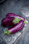 Three aubergines on a stone wall