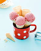 Homemade strawberry ice in cones and an enamel mug