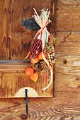 Bunter Mais mit Lampionfrüchten und Hagebutten als hängende Deko