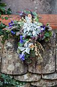 Bepflanztes Kreuz mit Silberblatt, Heide und Stiefmütterchen als Grabschmuck