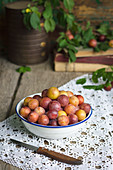 Fresh mirabelle plums in white bowl on a rustic wooden table