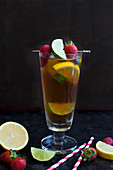 A tall glass of Pimms with lime and raspberry