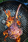 Tomahawk beef steak on a grill (top view)