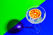 Blood orange slice in drink on green and blue backdrop