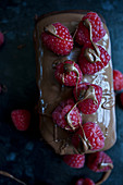 A chocolate cake topped with milk chocolate and raspberries