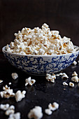 Popcorn in a blue and white bowl, spilling onto a black countertop