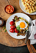 Hearty waffles with a fried egg, tomatoes, mushrooms and baked beans