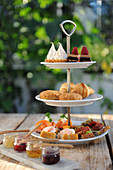 Various canapes and sweet pastries on a cake stand for tea (England)