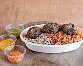 A falafel bowl with vegetables and a trio of dips