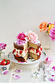 Strawberry rose layer cake topped with roses on a cake stand, slice taken out