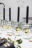 Schwarze Kerzen auf Einmachgläsern mit Christbaumkugeln