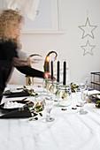 Frau zündet Kerzen an am weihnachtlich gedeckten Tisch
