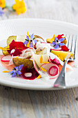 New potatoes with radishes, beetroots, kohlrabi, wine cheese, yoghurt dressing and edible flowers