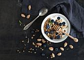 Granola mit Haferflocken, frischen Blaubeeren, Mandeln, Jogurt und Minze
