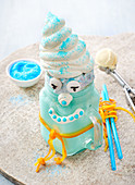 A blue Freak Shake decorated with a face and a cream hat