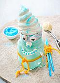 Blauer Freak Shake dekoriert mit Gesicht und Mütze aus Sahne