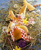 Sweet yeast dough Easter bunnies on hay with spring flowers