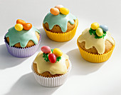 Colourful Easter muffins with icing and sugar eggs
