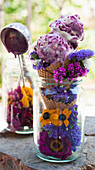 Fruits of the forest ice cream in a cone served with summer flowers in a jar