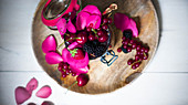 Semolina pudding with jam, berries and rose petals in a flip-top jar (seen from above)