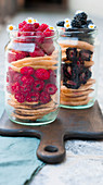 Pancakes layered with raspberries and blackberries in screw-top jars