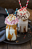 Two caramel freakshakes decorated with doughnuts