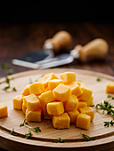 Diced Cheddar on a wooden board with thyme