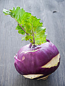 A purple kohlrabi on a grey wooden board