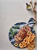 Mit Rosmarin gefülltes Rinderfilet mit Blauschimmelkäsesauce und Zwiebelringen