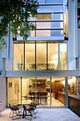 Blick von der Terrasse auf ein beleuchtetes Haus mit Glasfront