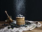 Pfannkuchenturm mit Blaubeeren und Minze mit Puderzucker bestreuen
