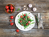 Salad with arugula, cherry tomatoes, sunflower seeds and herbs