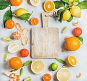 Viele verschiedene frische Zitrusfrüchte mit Blättern um ein Holzschneidebrett