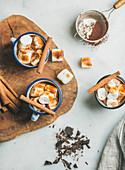 Heiße Schokolade mit Marsmallows und Zimt in Emaillebechern