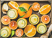 Healthy yellow smoothie with citrus fruit and ginger in bottles in wooden tray