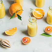 Healthy yellow smoothie with citrus fruit, ginger, ice in glass bottles