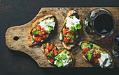 Bruschetta with grilled eggplant, cherry tomatoes, garlic, cream cheese, arugula and glass of red wine