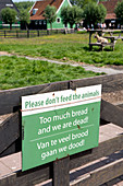 Do not feed the animals, bilingual warning sign