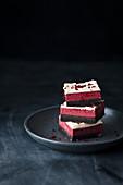 Red Velvet Cheesecake-Brownies auf Teller vor schwarzem Hintergrund