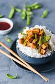 Sweet and sour tofu with mange tout on rice (Asia)